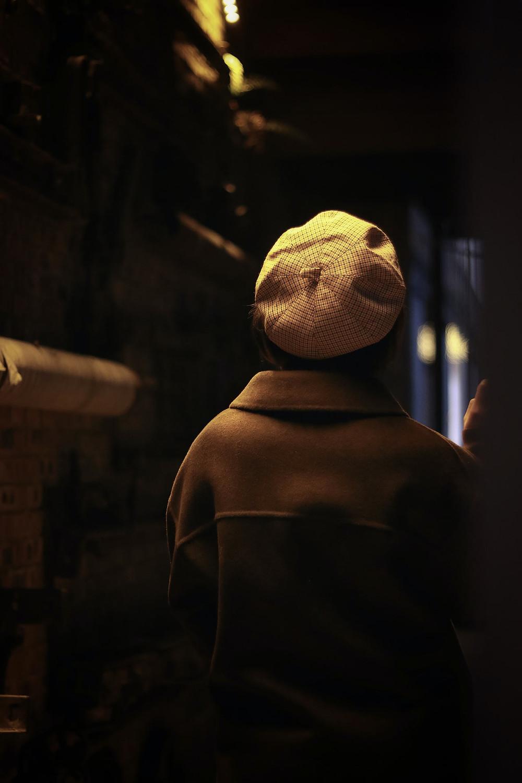 Henkilö baskeri päässä selkä kohti kameraa hämärässä bussin valaistuksessa.