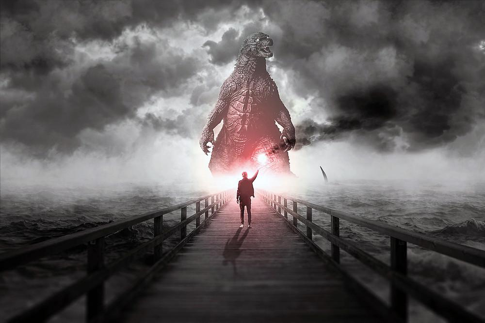 Kuvituskuva. Godzilla nousee meresta. Kuvan etualalla puisella sillalla mies, joka pitää kädessään punaista hätäsoihtua.