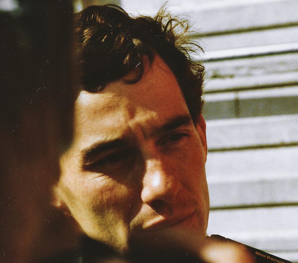 Lähikuva vakava kasvoisesta tummahiuksisesta Ayrton Sennasta.