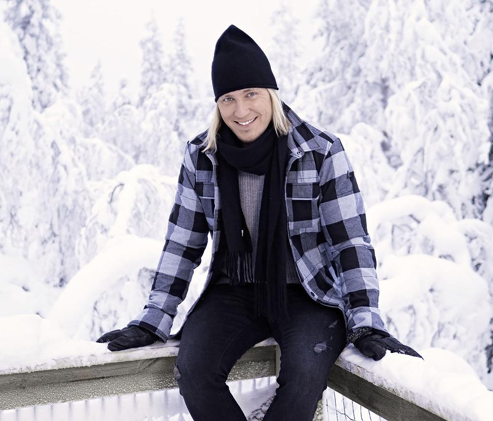Temptation Island -ohjelman juontaja Sami Kuronen istuu lumisella aidankaiteella taustallaan luminen maisema.