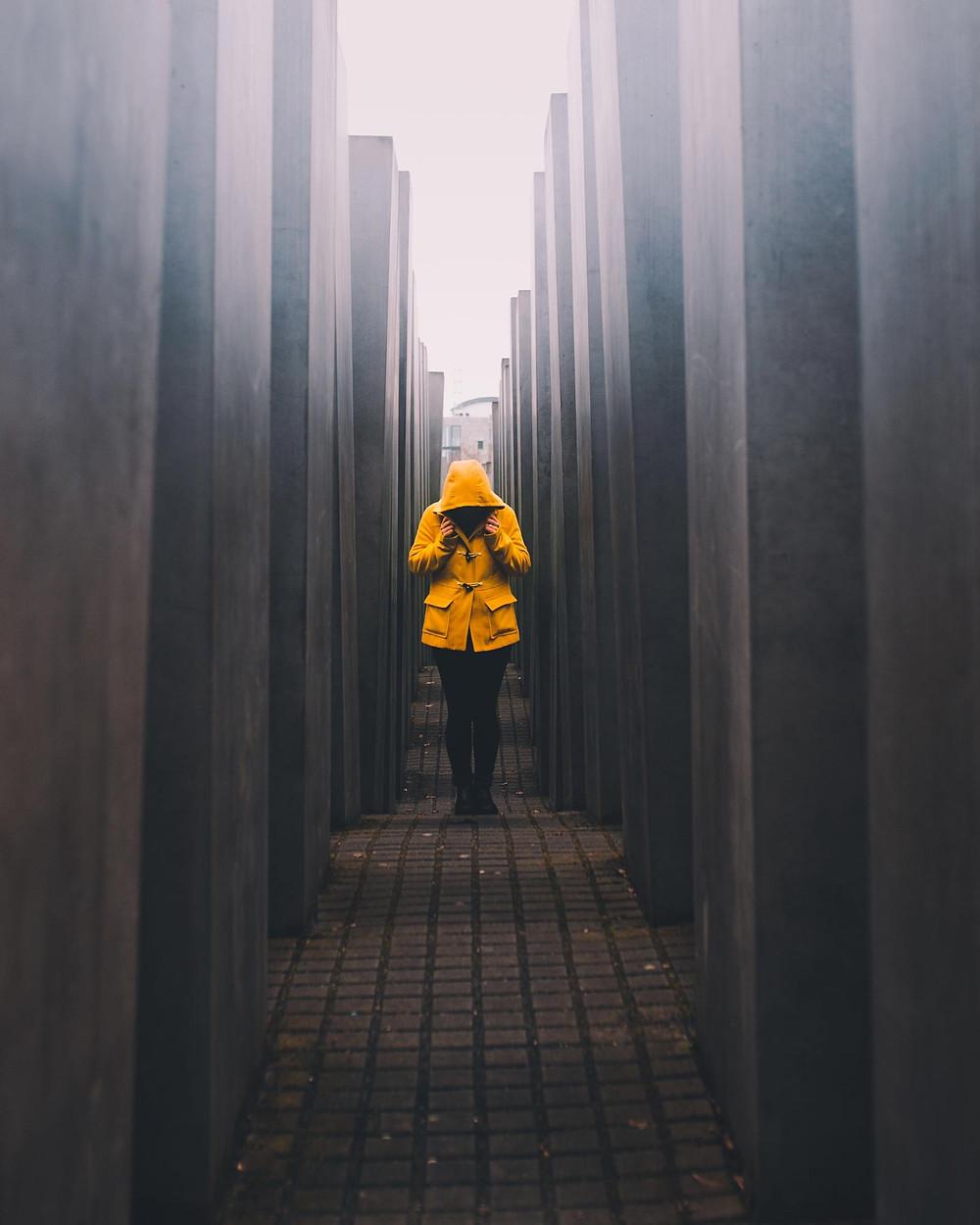 Kuvituskuva: Keltaisessa takissa oleva henkilö seisoo huppu päässä kapealla kujalla. - kuva unsplash.com