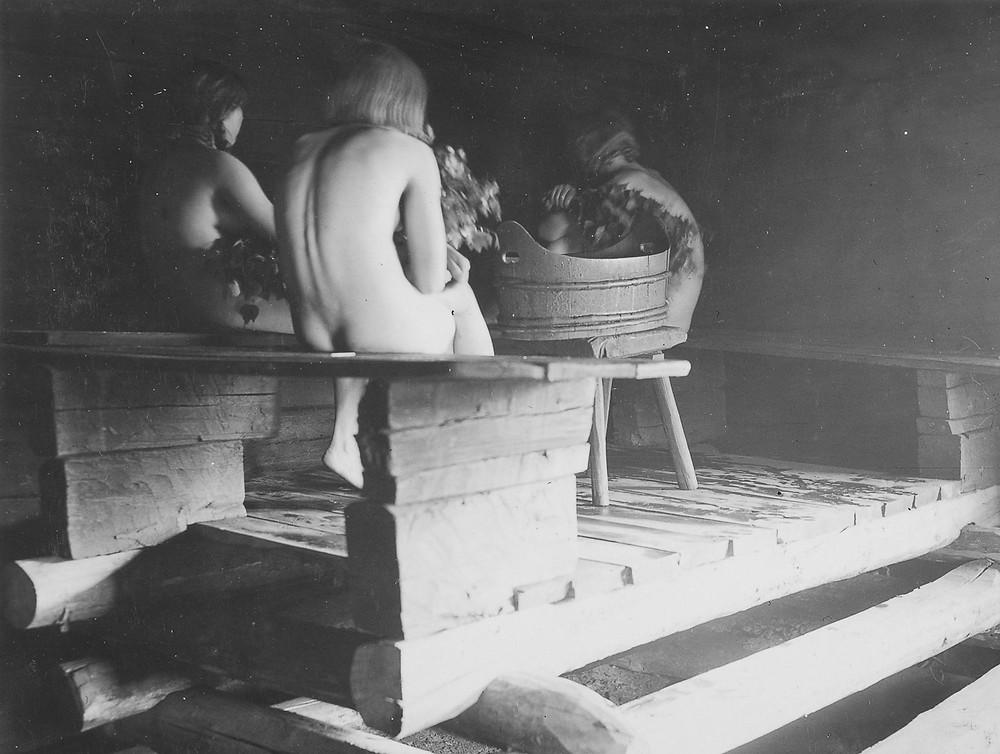 Mustavalkokuvassa piiat istuvat saunassa selkä kameraan päin.