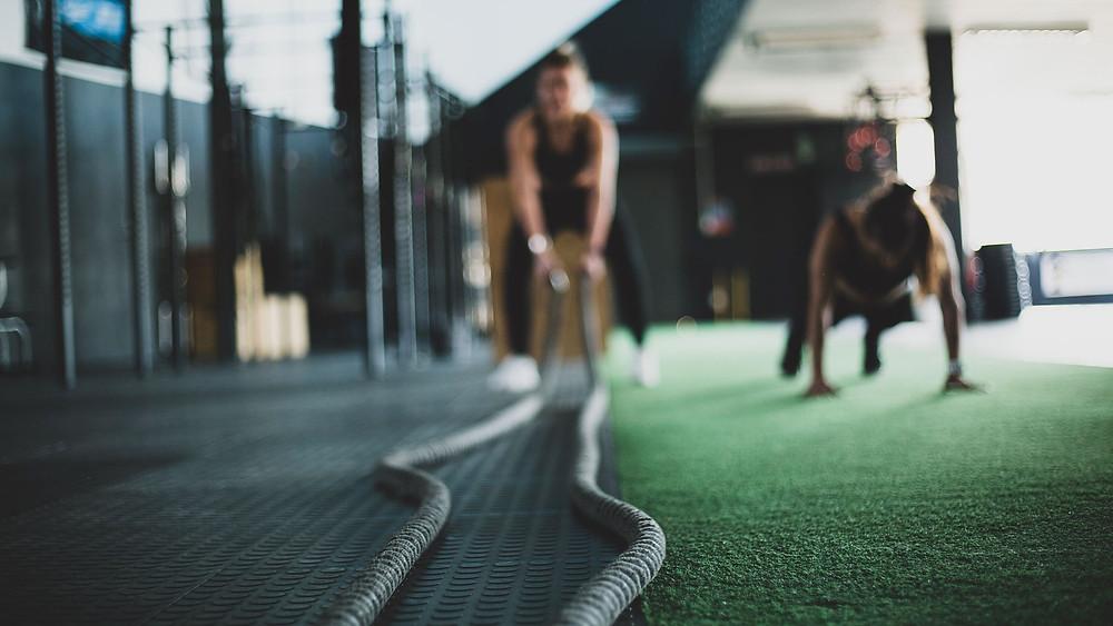 Kuva kuntosalilta. Urheilija heiluttaa käsillään kahta pitkää ja painavaa köyttä.