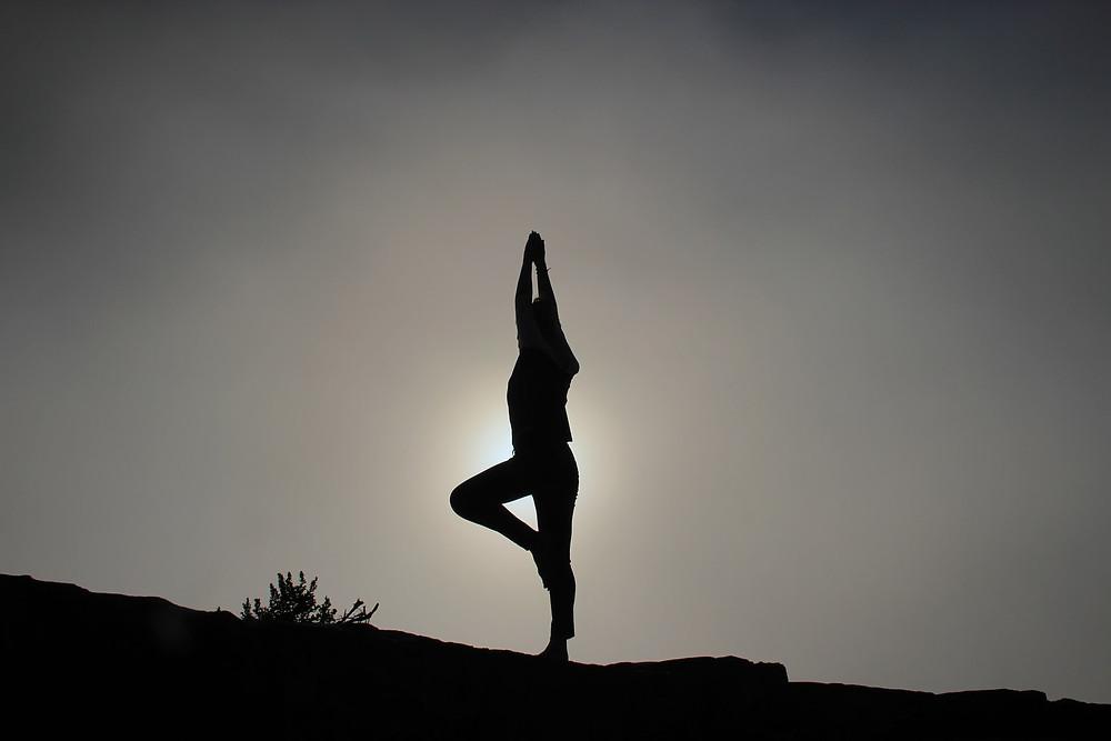 Joogaaja auringon edessä. Kädet yhdessä kohti taivasta, toinen jalka maassa ja toisen jalan jalkapohja asetettuna toisen jalan polven päälle.