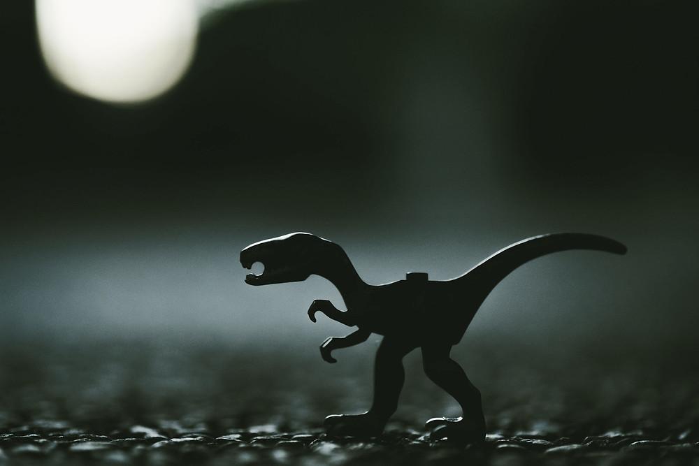 Mustavalkoisessa kuvassa leludinosaurus keskellä huonetta.