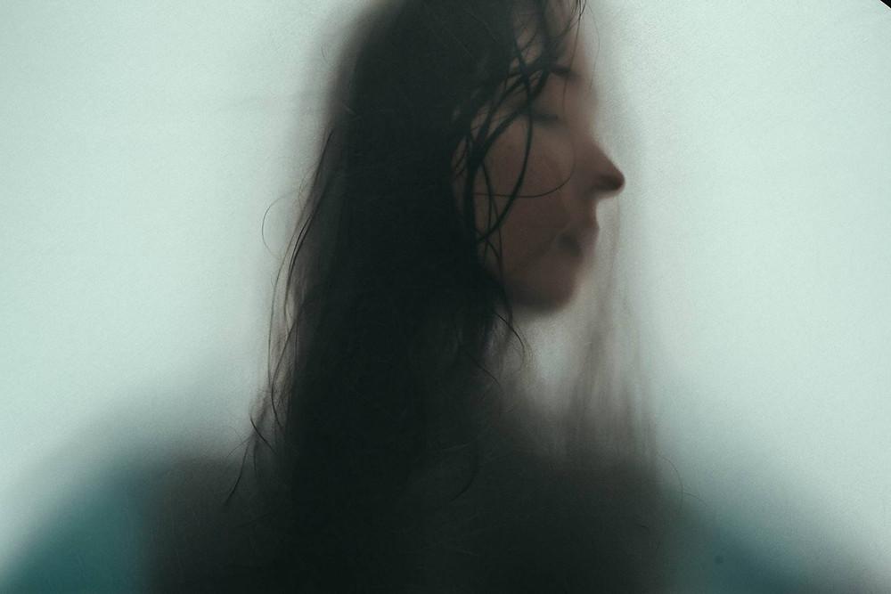 Kuvituskuva: Naisen kasvot vasten lasia. - Unsplash