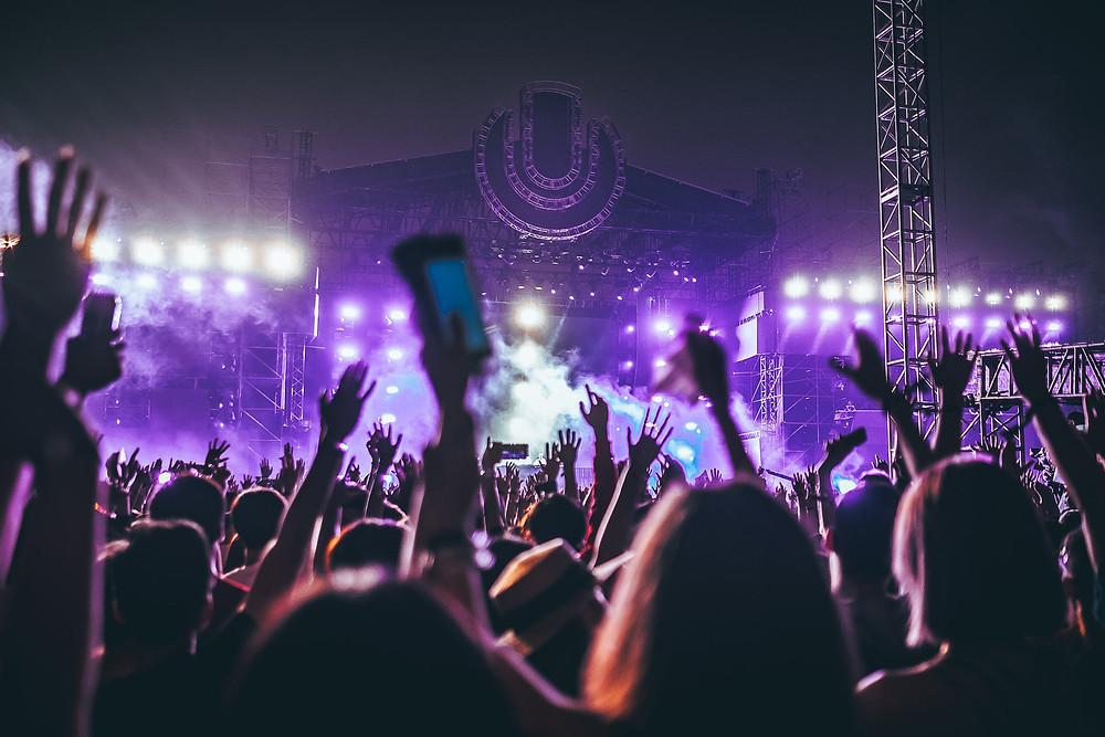 Kuvituskuva musiikkifestivaaleista. Lava violetissa valossa ja käsiä ilmassa.