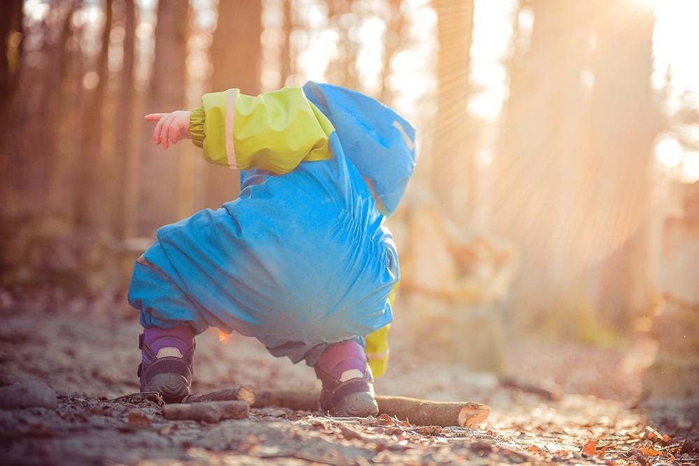 Kuvituskuva. Lapsi sinisessä kurahaalarissa ottaa keppiä maasta.