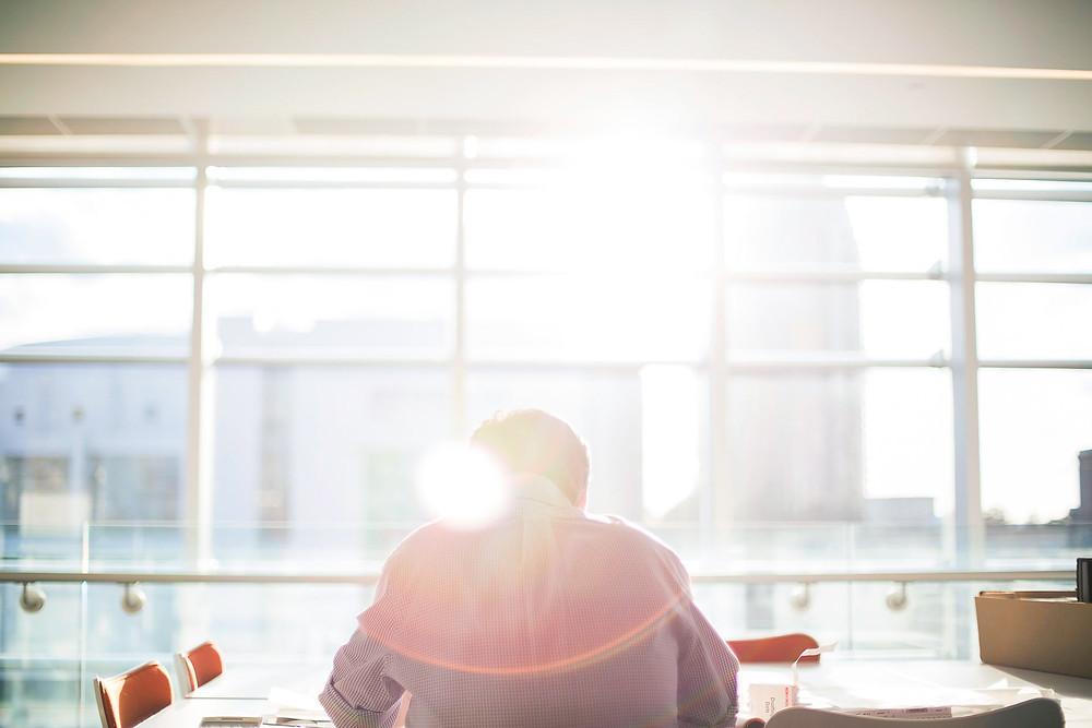 Mies istuu toimistossa isoa ikkunaa vasten auringonpaisteessa.