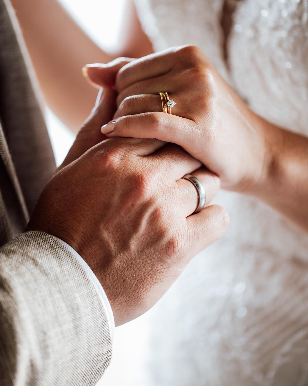 Kuvassa hääpuvussa oleva nainen ja puvussa oleva mies pitävät toisiaan kädestä. Kaunis kultainen timanttisormus ja miehen hopeinen sormus etualalla.
