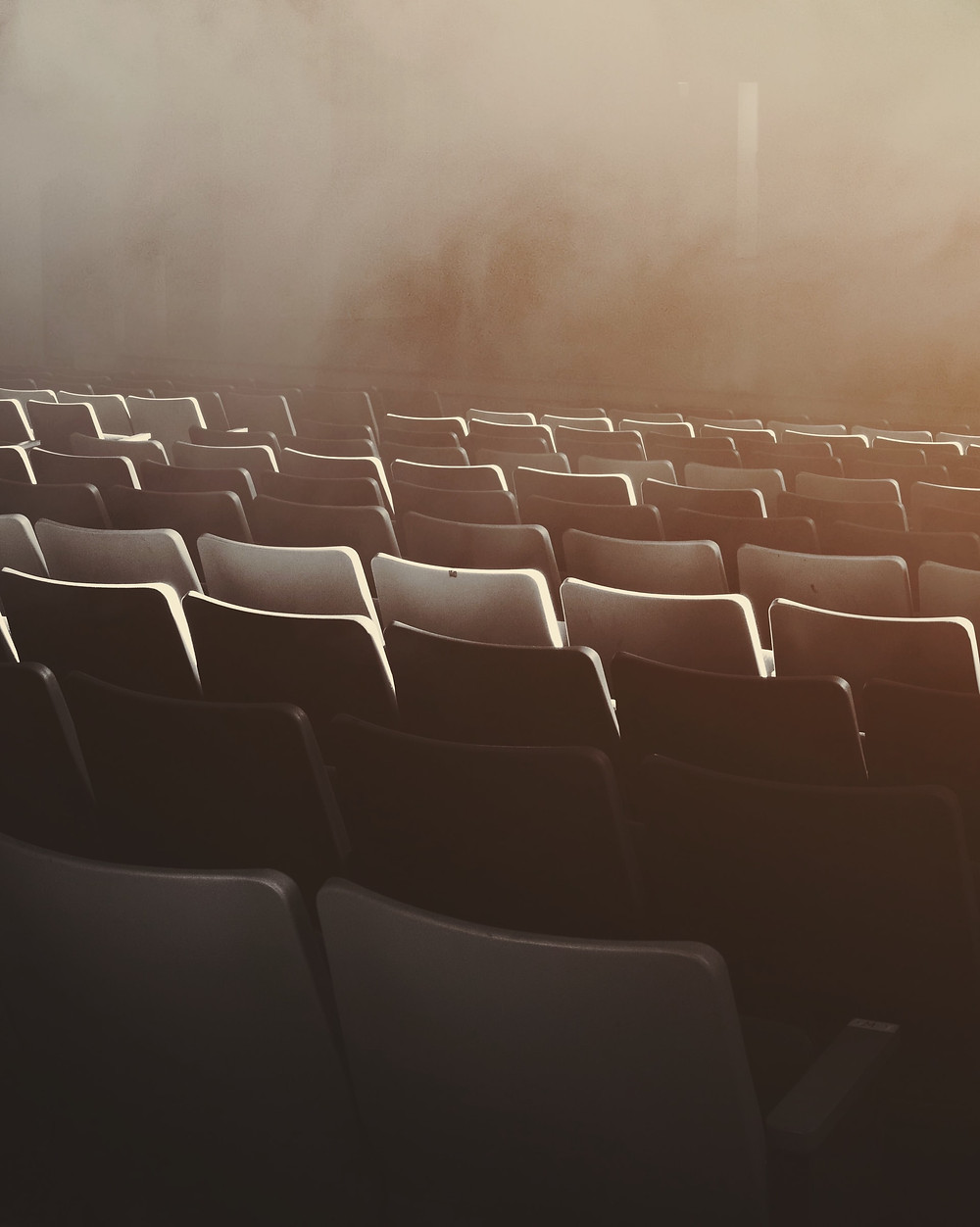 Teatterikatsomon tuoleja pinottuna päällekäin riveissä selkäpuoli kameraan päin.