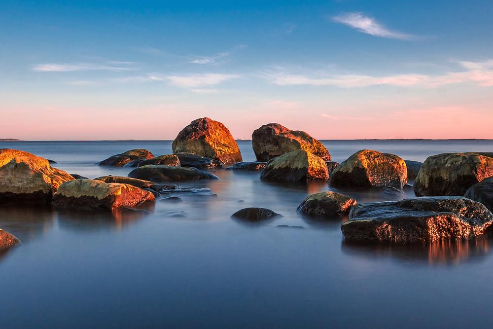 Kuvituskuva. Merenranta, jossa vedestö nousee eri kokoisia kiviä.
