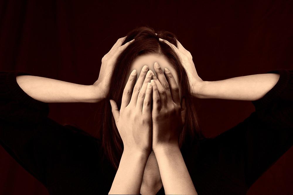 Kuvassa nainen pitelee käsiään kasvoillaan. Toiset kädet pitelevät hänen päätään turhautuneena.
