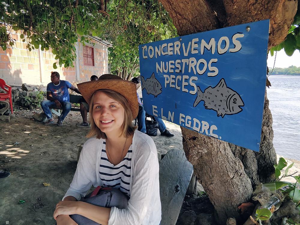 Maria Mountraki istuu puun juurella olkinen lierihattu päässään. Puussa on sininen kyltti, jossa on kaloja ja espanjan kielistä tekstiä.