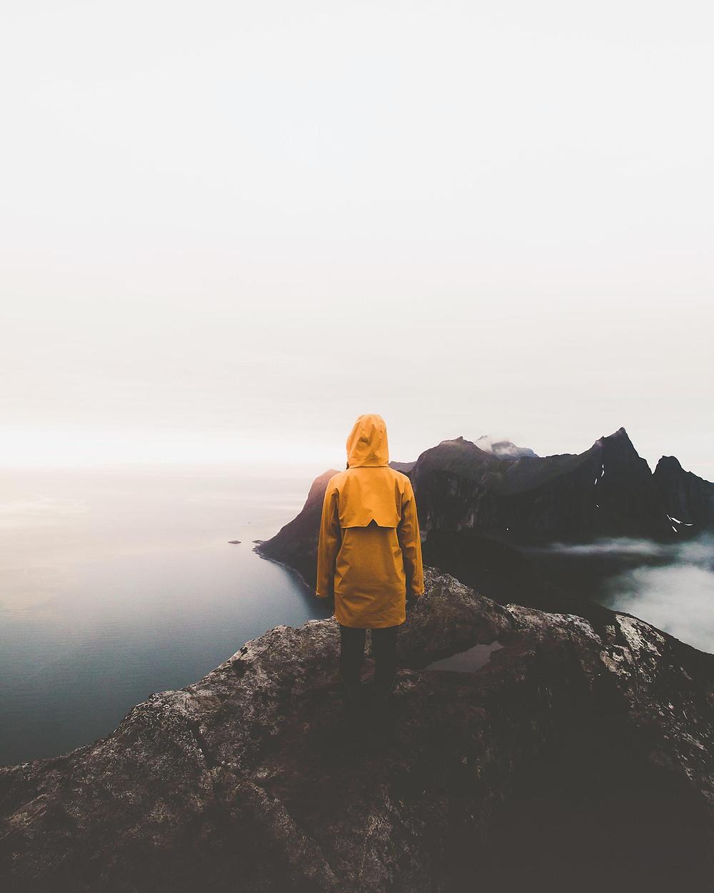 Kuvituskuva: Henkilö keltaisessa takissa katsoo kalliolta merelle. - kuva unsplash.com
