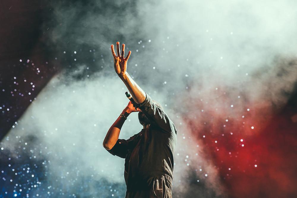 Kuvituskuva. Laulaja laulaa mikkiin toinen käsi ylhäällä valkopunaista sumuista taustaa vasten.