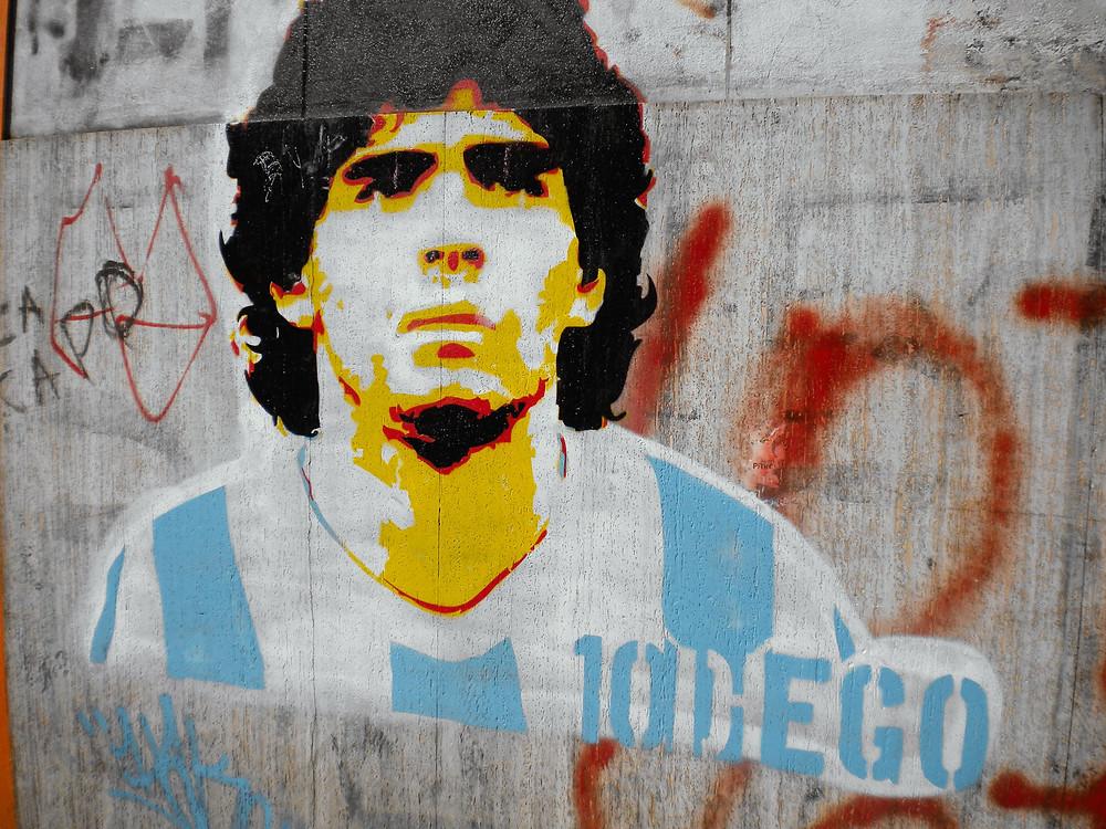 Betoniseinään maalattu näköiskuva tummahiuksisesta argentiinalaispelaaja Maradonasta nuorena.