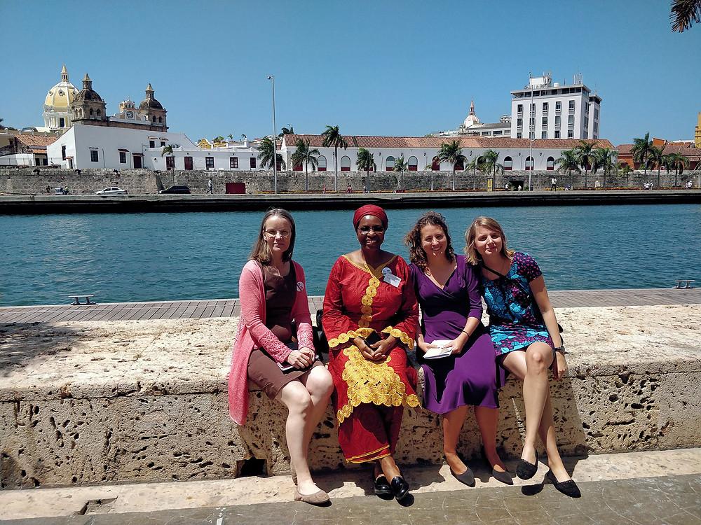 Kuvassa neljä naista istuu kaupunkia halkovan joen rannalla.