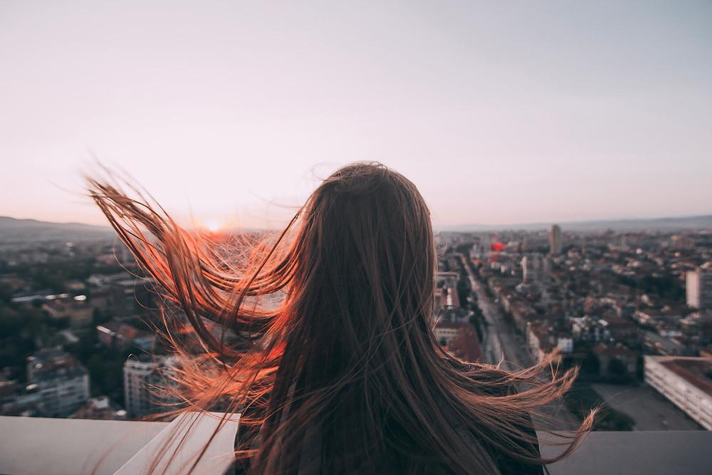 Kuvituskuva. Punahiuksinen nainen katsoo kaupungin ylle. Hiukset hulmuavat tuulessa.