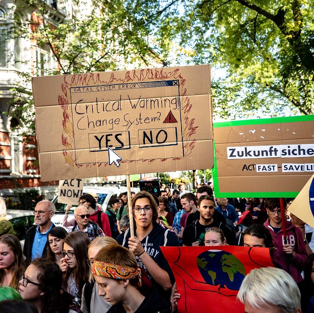 Nuori mies pitää kädessään kylttiä, johon on piirretty varoitus ilmaston kriittisestä lämpeämisestä. Kyltti kysyy, muutetaanko systeemiä.