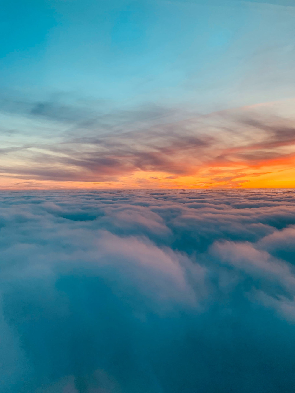 Kuvituskuva. Pilvien yläpuolelta kuvattu auringonlasku, jossa auringon säteet pilkistävät pilvien välistä.
