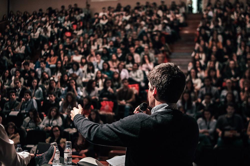 Kuvituskuva. Poliitikko puhuu suurelle yleisölle selkä kameraa kohti.