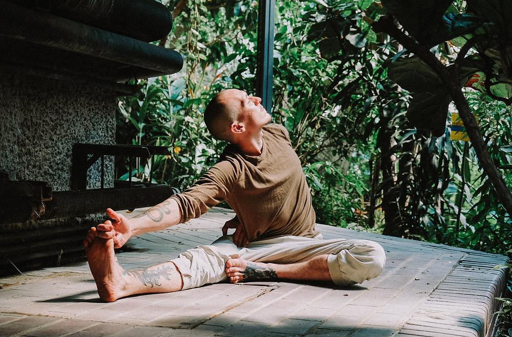 Mies joogaamassa puisella alustalla ulkona. Istuma-asennossa, jossa pitää kädellään yhden jalan varpaista kiinni. Pää katsoo jaloista poispäin kohti aurinkoa.