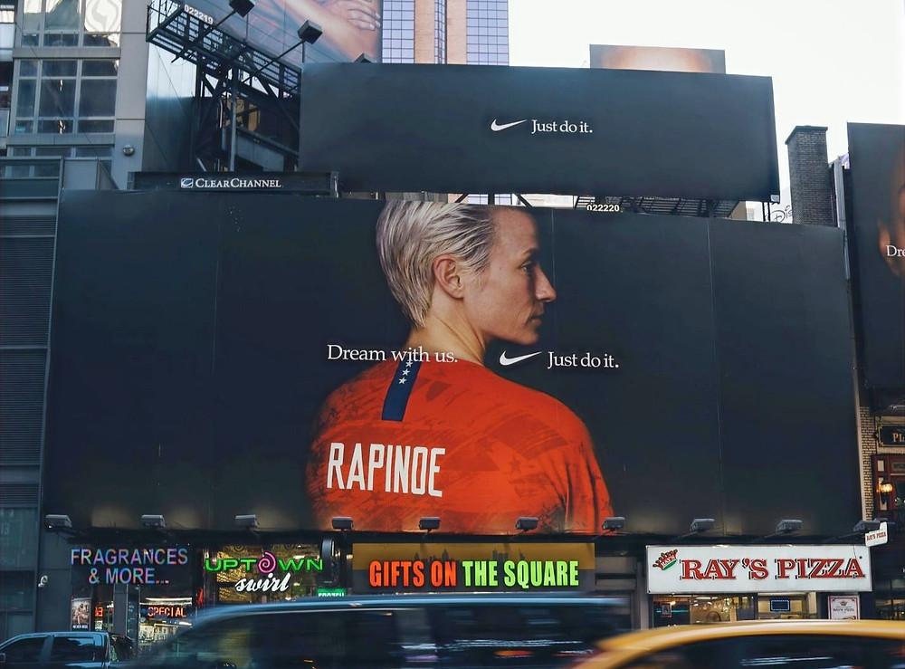 Kuvassa Megan Rapinoe punaisessa pelipaidassaan mainostaulussa.