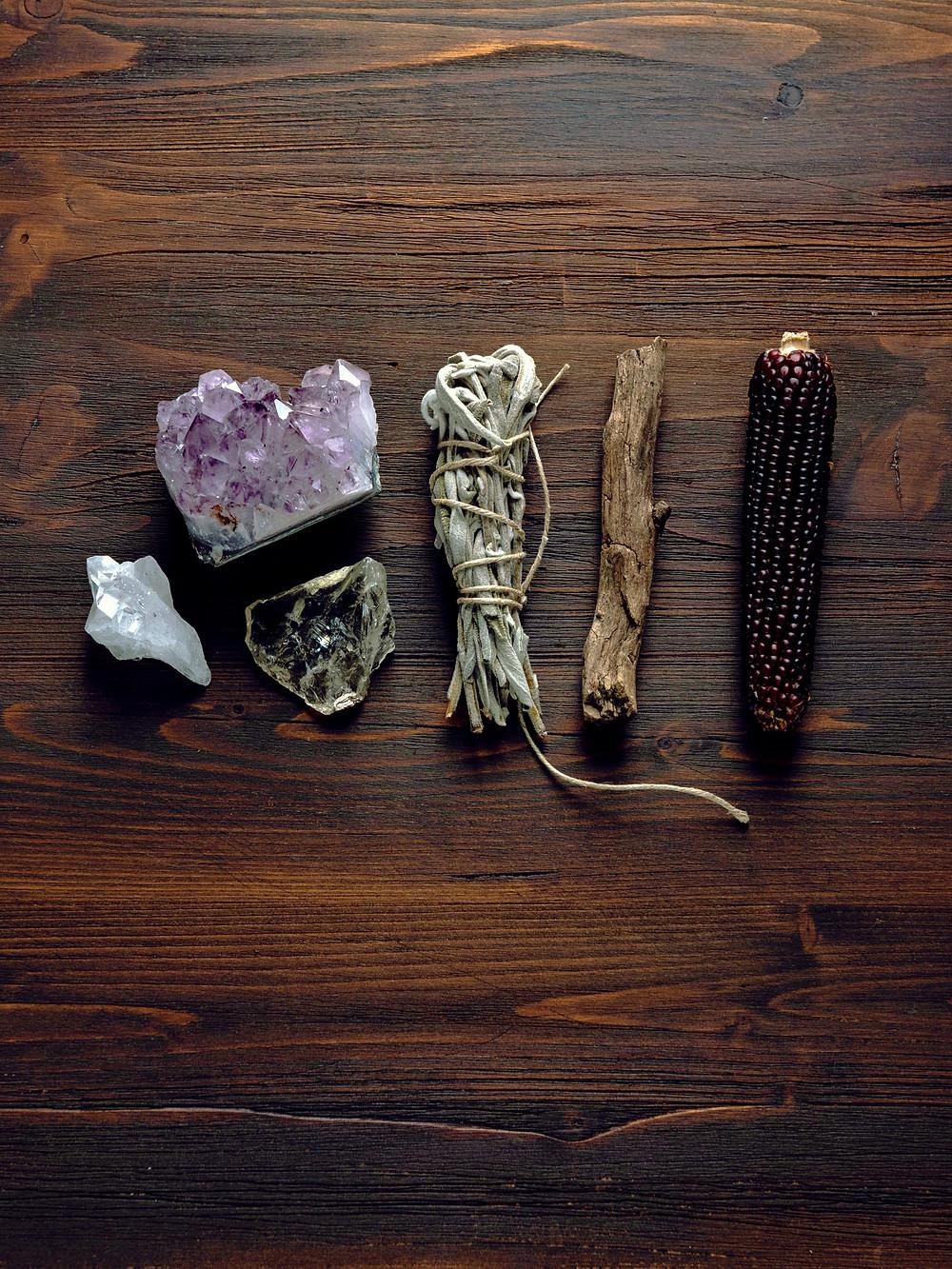 Kuvassa eri uskomushoitoihin käytettäviä esineitä kuten kristalleja ja kuivattuja lehtiä.