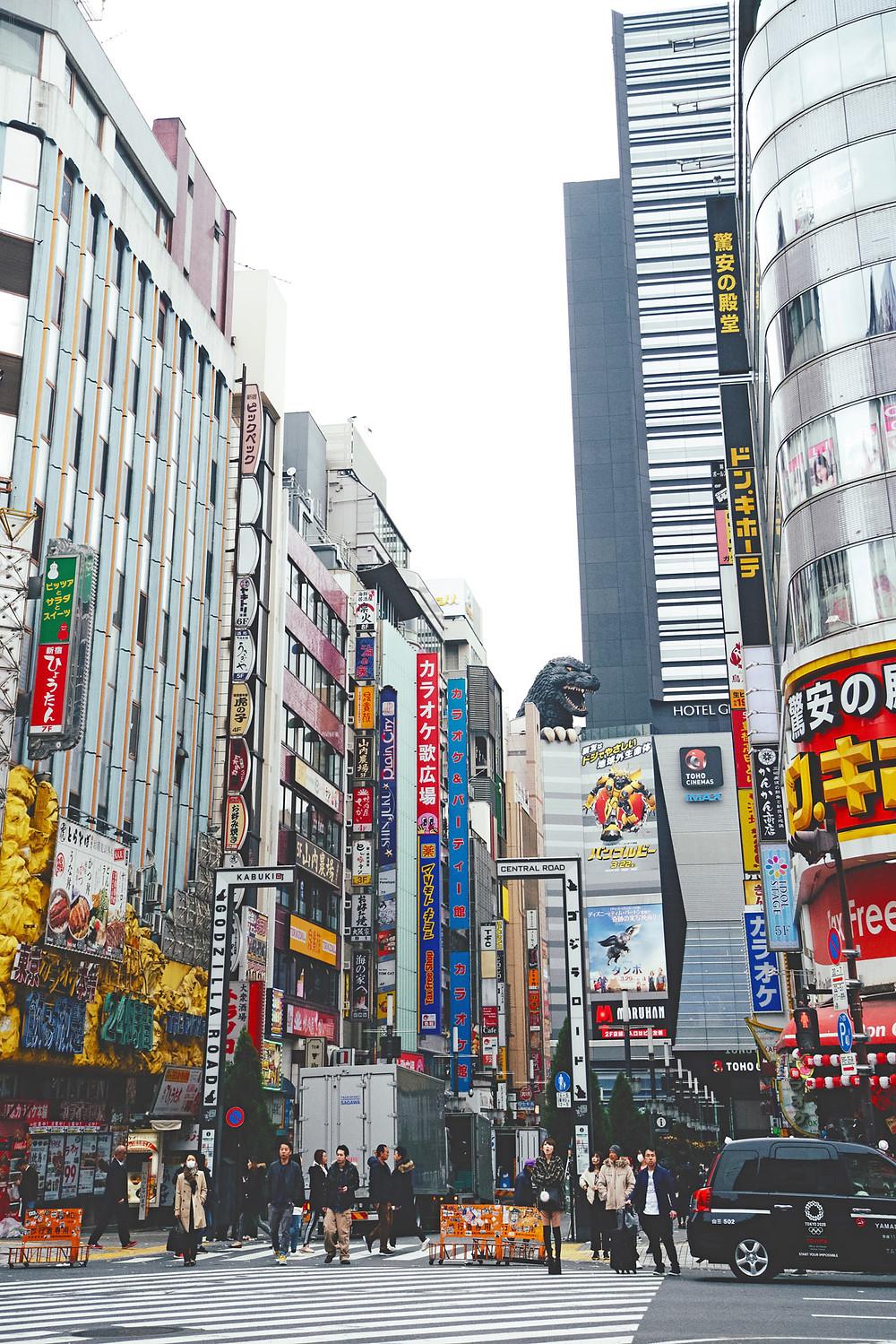 Kuvituskuva. Japanin katukuvassa korkeita taloja ja mainoskylttejä. Talojen takaa pilkistää Godzilla-hirviön tumma liskomainen pää.