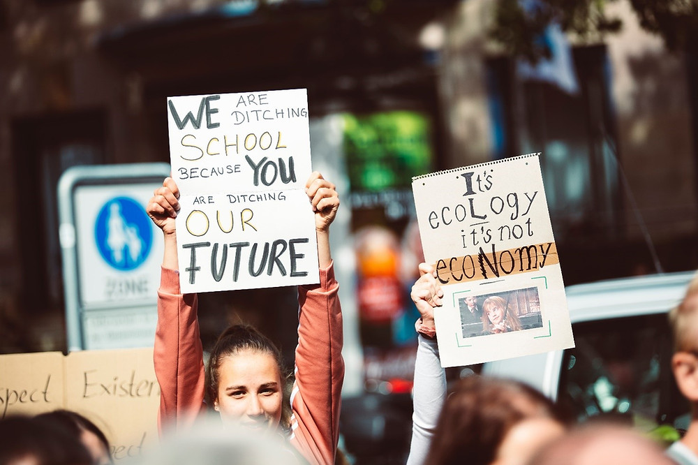 """Nuori nainen pitää kädessään kylttiä, jossa lukee """"We are ditching school because you are ditching our future."""""""""""