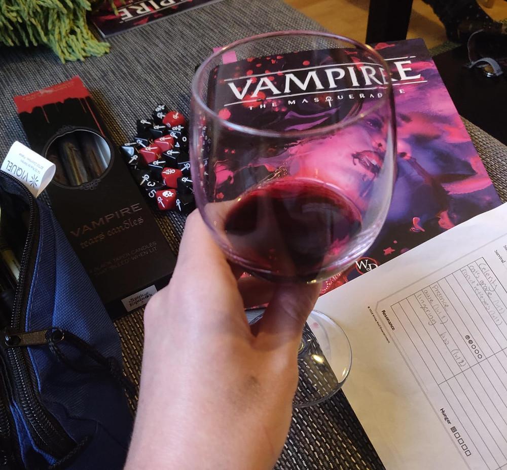 Kuvituskuva. Viinilasi, jossa punaviinia ja roolipelin ohjekirja ja noppia.