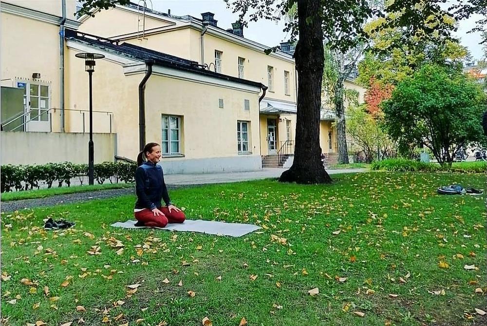 Katja Lilja istuu istuu polvillaan joogamatolla nurmikolla keltaisen rakennuksen edessä.