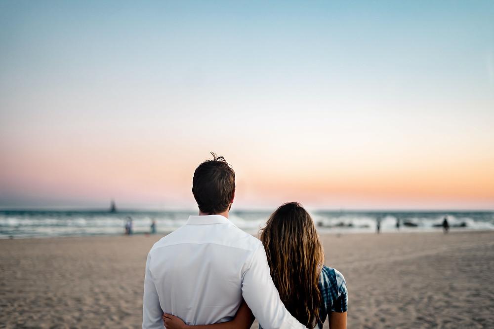 Kuvassa mies ja nainen katselevat yhdessä rannalla merta ja aaltoja.