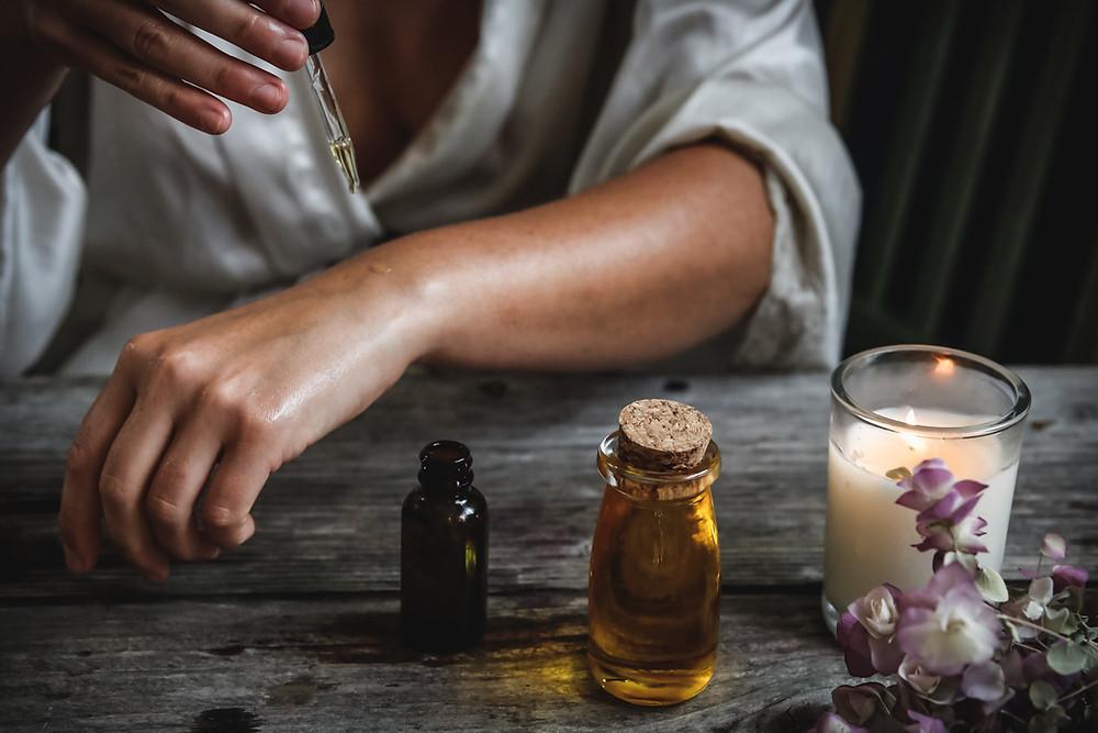 Kuvassa henkilö tiputtaa pipetillä öljyä kädelleen kynttilän palaessa pöydällä.
