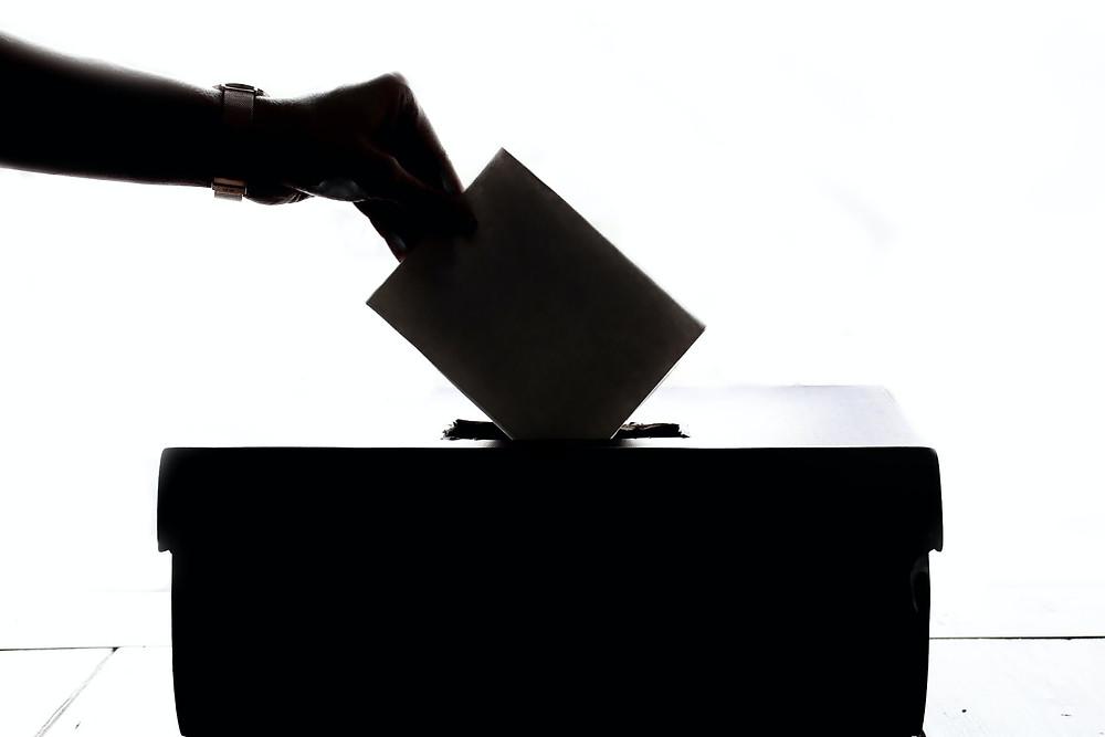 Mustavalkoisessa kuvituskuvassa käsi laittaa äänestyslipuketta vaaliuurnaan.