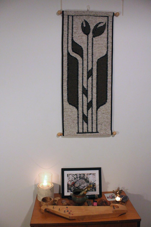 Kotialttari. Alttarin takana seinällä ryijy. Alttarilla on Juuso-karhun taideteos, kantele, riimuja, isoäidin kuva sekä kynttilä.