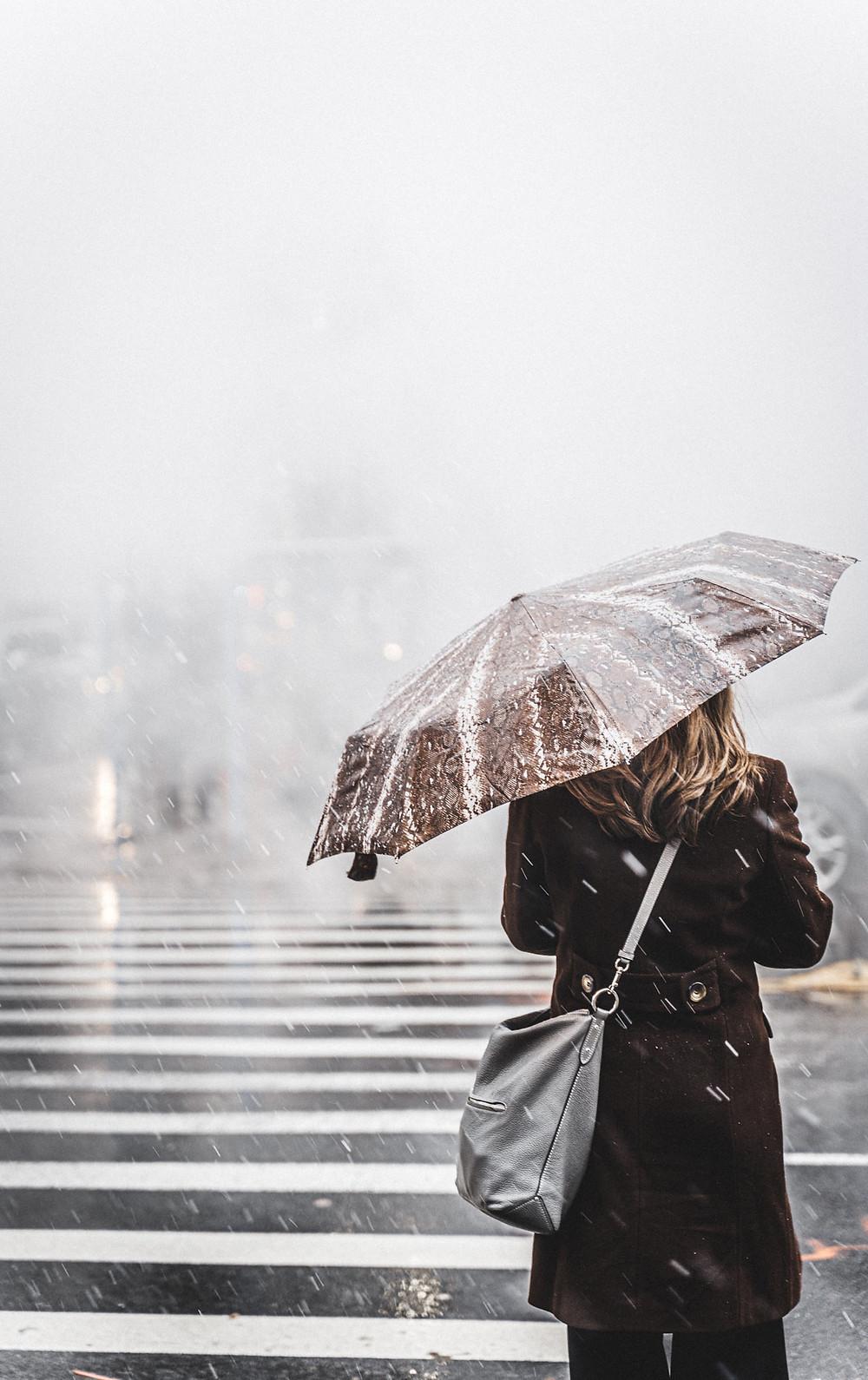 Nainen yksin vesisateessa ylittämässä suojatietä.
