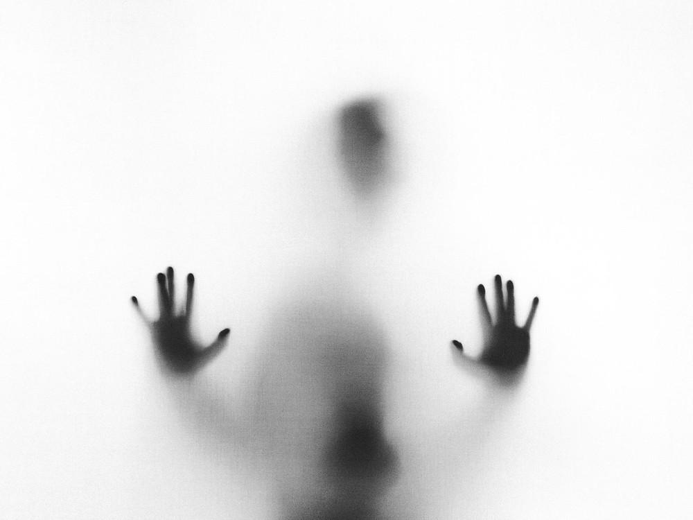 Kuvituskuva. Hahmo valkoista lakanaa vasten. Henkilön kädet ja keho näkyy tummana valkoista vasten.