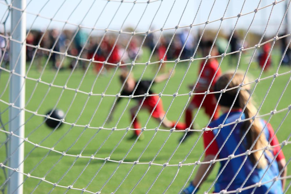 Lasten jalkapallopeli. Kuvassa maalivahtityttö torjumassa saapuvaa palloa.