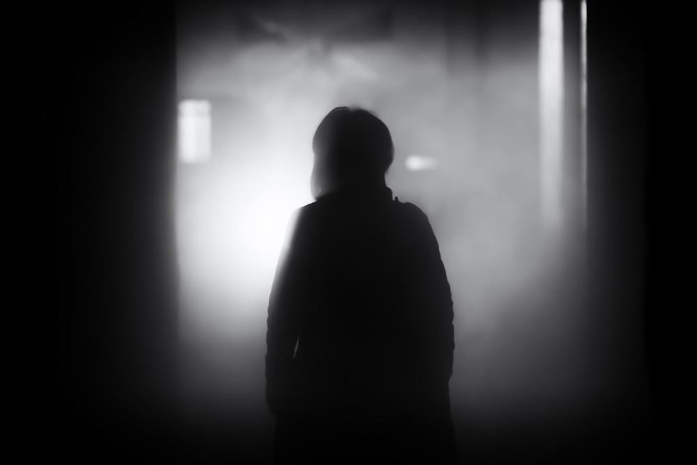 Mustavalkoinen kuva, jossa henkilö katsoo sumuun.