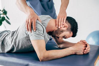 chiropractor-massaging-shoulder-and-neck