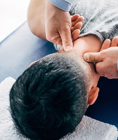 chiropractor-massaging-neck-of-man-lying