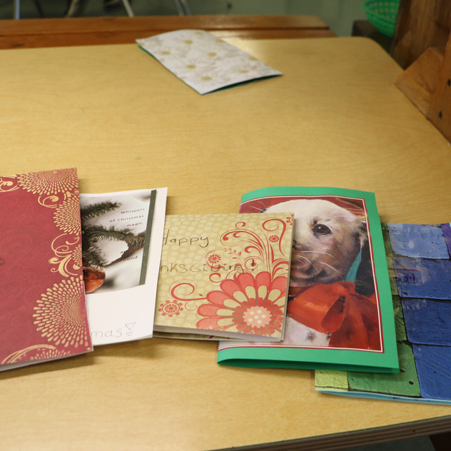 Cards of all different styles are lined up on the table awaiting their shipment and distribution.