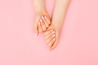 Hands of a beautiful woman on a pink bac