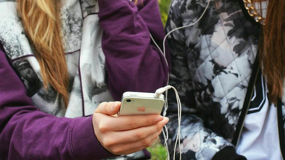 Lecture en ligne de webroman par adolescentes sur téléphone