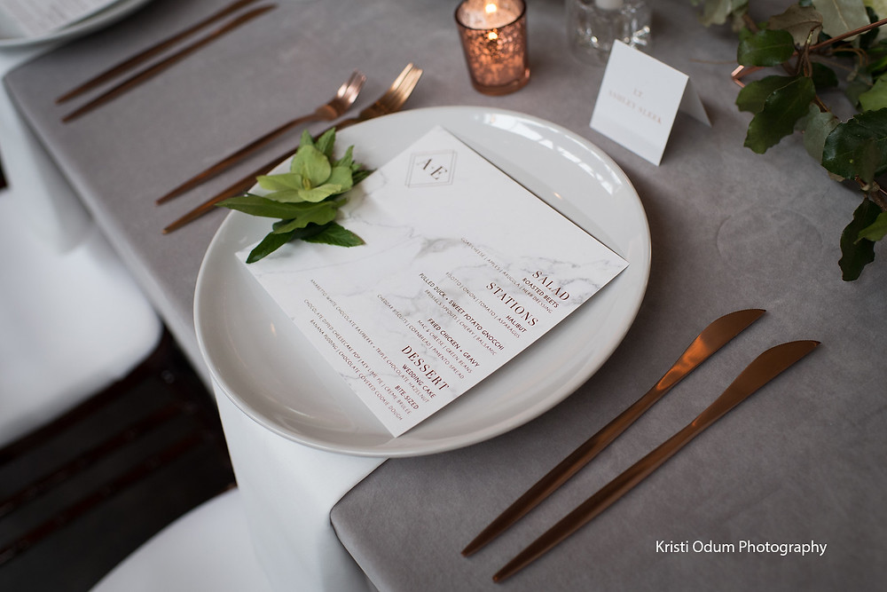 Copper themed wedding tablescape with menu and place card with a touch of greenery.