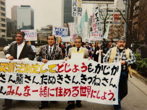 """<< Let's enact a new Ainu law and make the world a place where loaches, deer, bears, raccoons, and foxes can all live together. >>   On March 27, 1992, 250 Ainu living in Hokkaido and the Tokyo metropolitan area marched to demand the immediate repeal of the """"Old Ainu Protection Law of Hokkaido"""" and the enactment of the """"New Ainu Law""""."""