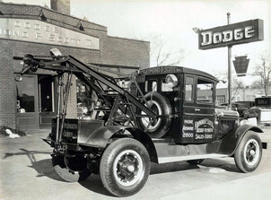 Black-and-white-tow-truck-infront-of-dodge-dealership