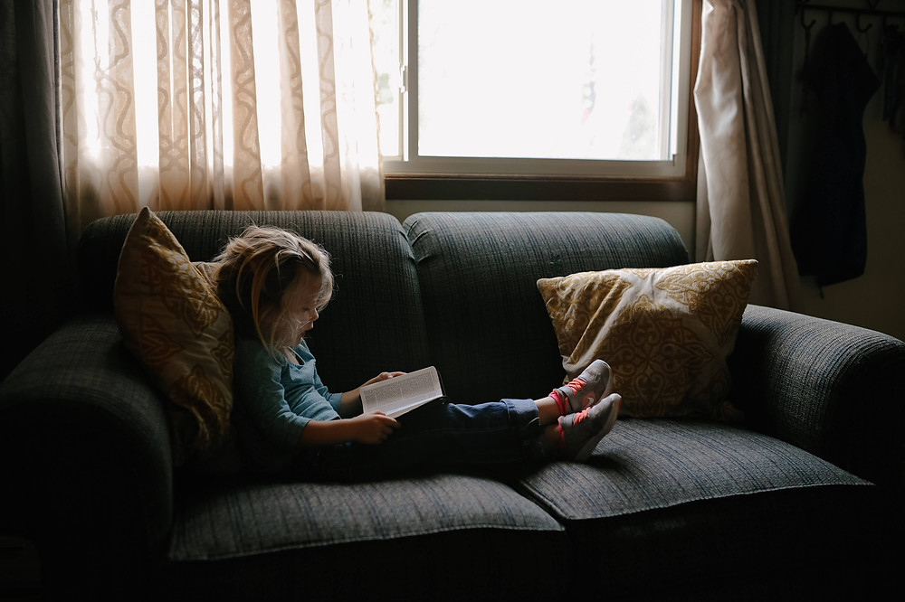 child reading quietly on the couch